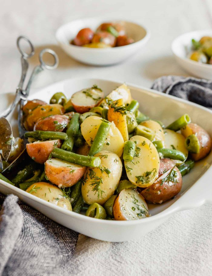 Side angle image of green beans, potatoes, lives and herbs in a white square dish set on a table.