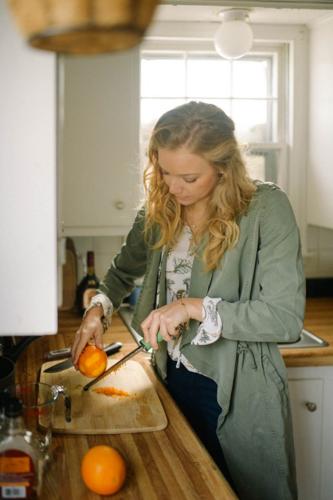 photograph of woman in a green coat in a kitchen zesting an orange