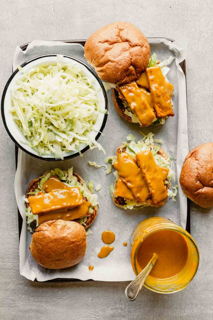 baking sheet lined with parchment paper with bbq sandwiches, slaw and bbq sauce set on top