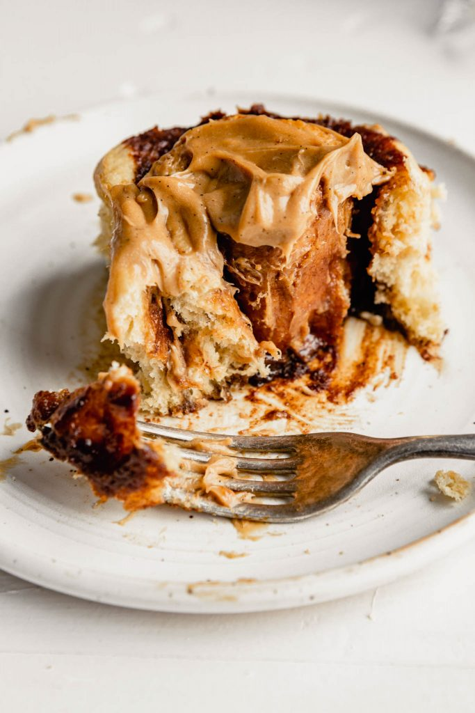 close up image of a frosted cinnamon roll on a white plate with fork cutting into it