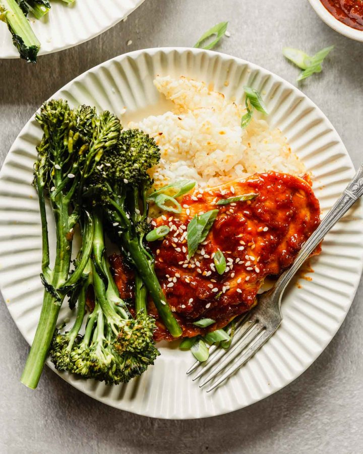 chicken breast coated in a red sauce plated over rice with broccolini in an off-white bowl