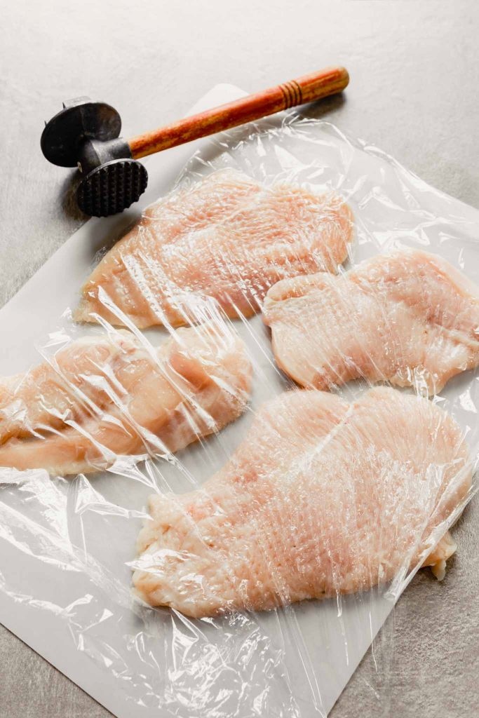 raw chicken breast on cutting board covered with plastic wrap
