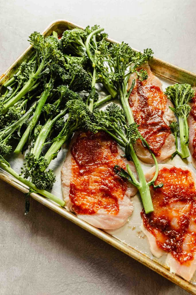 raw chicken topped with red sauce arranged on a baking sheet with broccolini arranged around it
