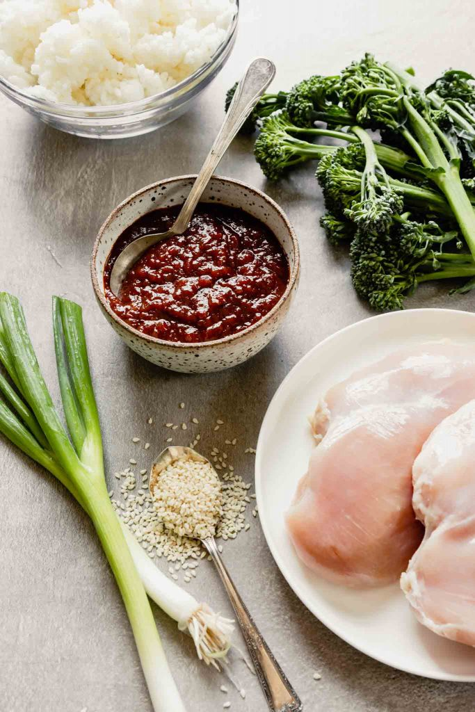 chicken breast, gochujang sauce, broccolini, sesame seeds and rice set on a gray table
