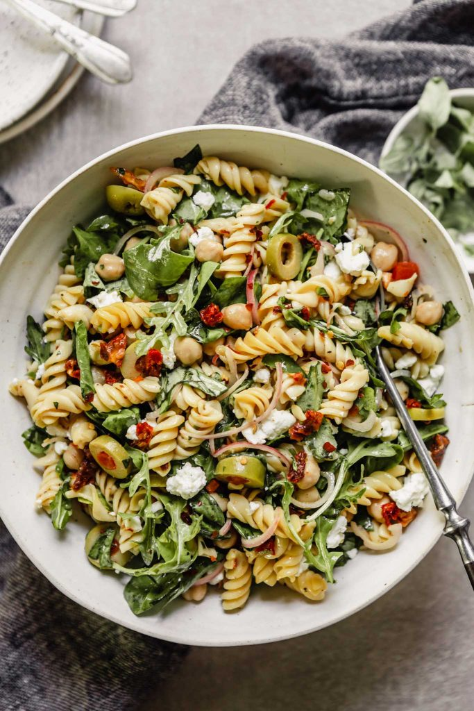 pasta, spinach, olives and sun dried tomatoes in a white bowl set on top of a napkin