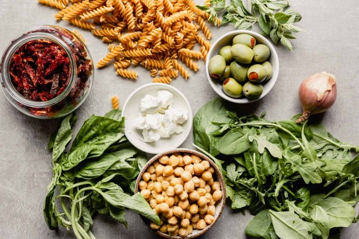 image of dry pasta, sun dried tomatoes, olives, chickpeas, spinach, basil and oregano arranged on a counter top