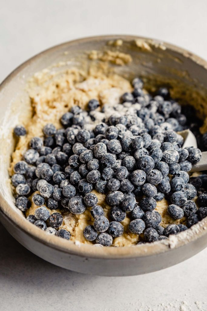 blueberries coated in flour poured over top of muffin batter