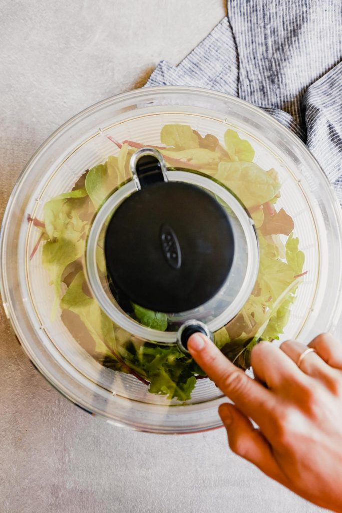 image of a hand stopping a salad spinner from spinning