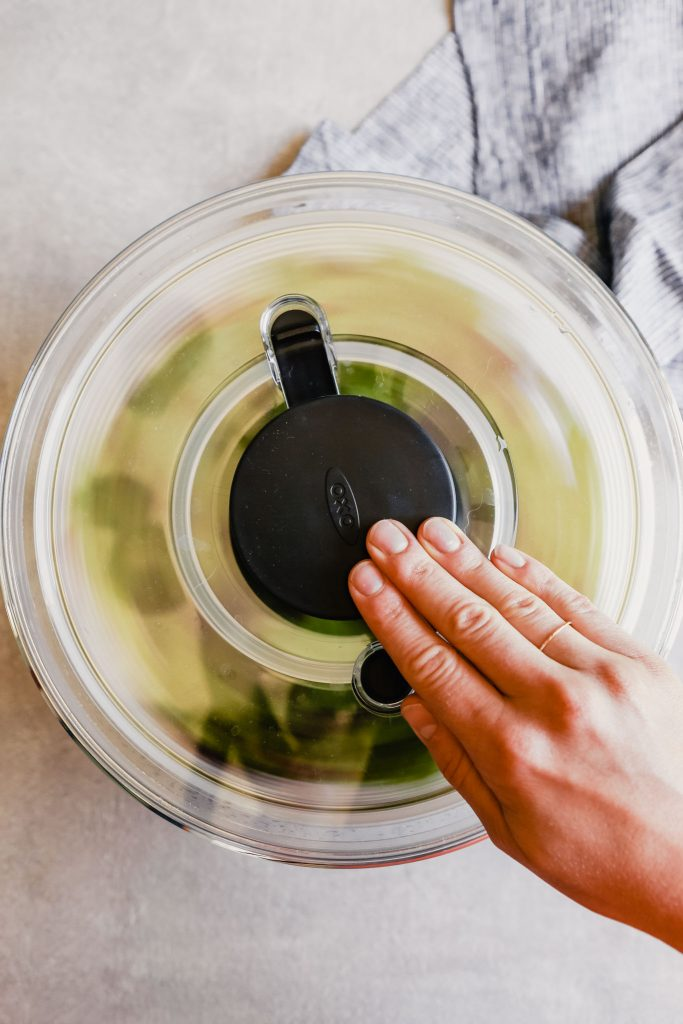 a hand pressing a salad spinner down to spin