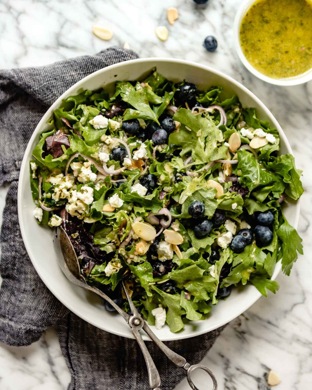 image of a green salad in a large white bowl topped with blueberries, almonds, cheese and sliced shallots