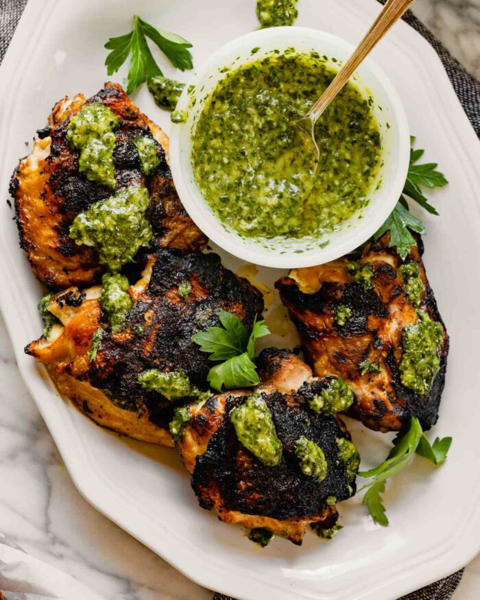 Grilled chicken thighs on a white plate drizzled with chimichurri sauce with a bowl of green sauce off to the side
