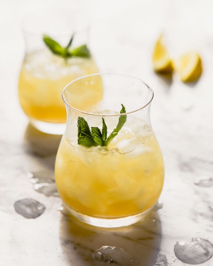 Yellow-colored cocktail in a whiskey glass with crushed ice and a mint sprig.