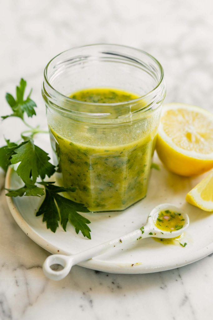 image of a yellow vinaigrette in a glass jar set on a white plate