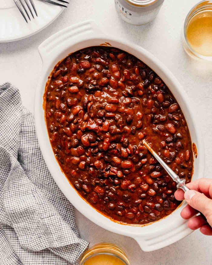 baked beans in a white oval dish with a spoon in them