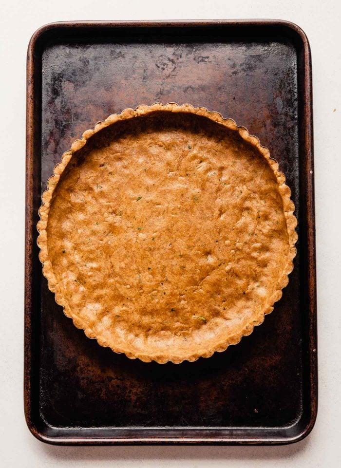 unbaked tart crust on a baking sheet