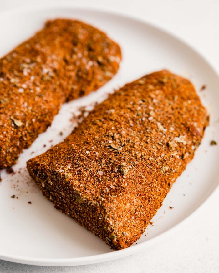 fish fillets coated in a spice blend set on a white plate