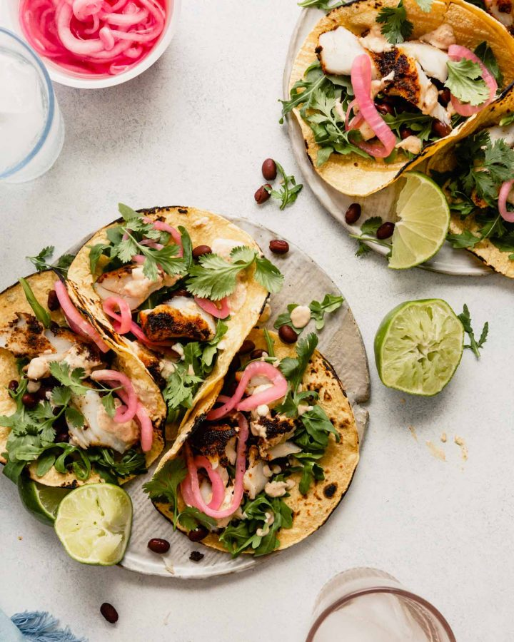 tacos arranged on a flat white plate topped with pickled onions, black beans and arugula