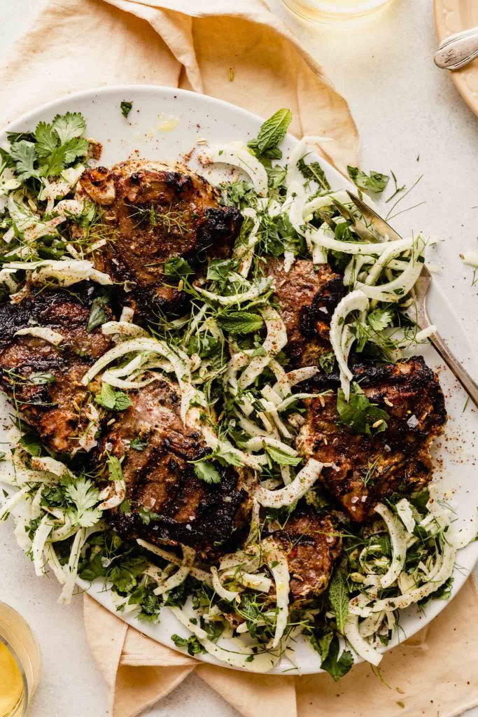 grilled lamb chops arranges over thinly sliced fennel on a white plate