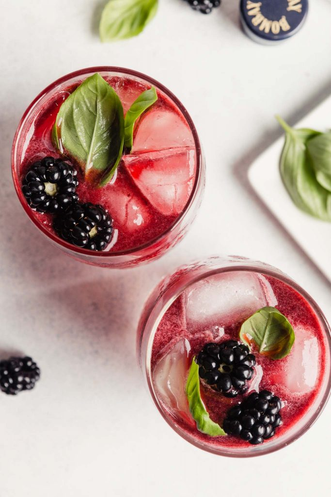 pink cocktail in a tall glass topped with blackberries and basil leaves