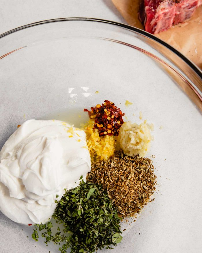 yogurt, lemon zest, spices and herbs in a large glass bowl