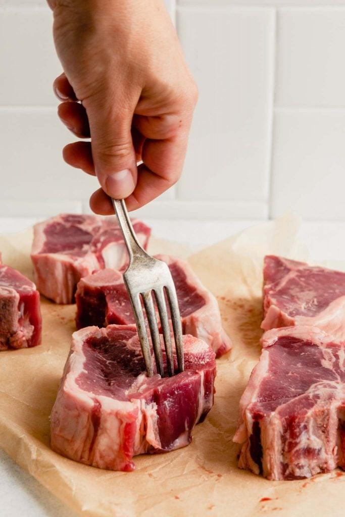 a fork piercing lamb chops