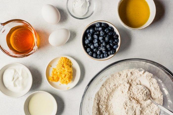 blueberries, honey, eggs, yogurt, flour, baking soda, oil, and yogurt measured out for cooking