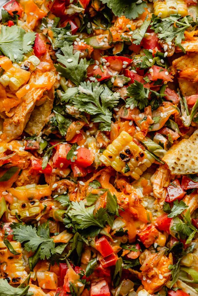Close up picture of all the toppings on korean nachos including cilantro, tomatoes, chicken, cheddar, kimchi, green onions, and charred corn.
