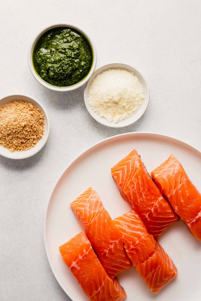 image of salmon fillets on a plate with bowls of pesto, parmesan and bread crumbs set around it