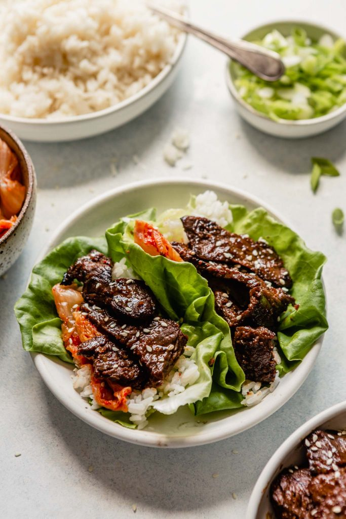 white bowl with lettuce wraps filled with rice, kimchi and grilled beef bulgogi. Set on a table with bowls of rice, scallions, and kimchi set around