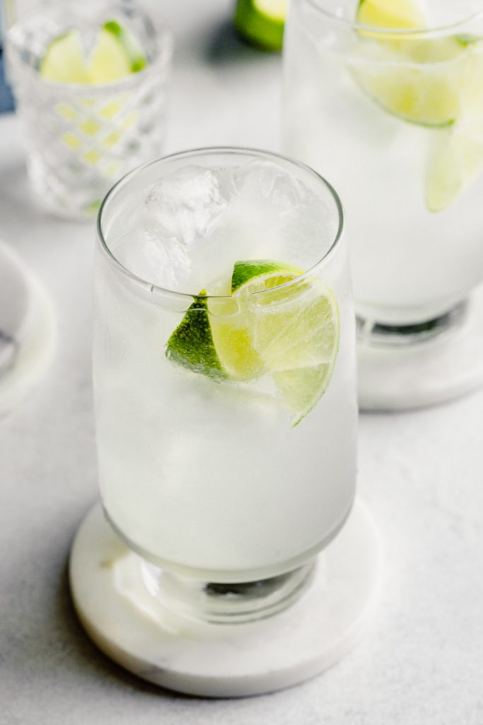 tall glass filled with ice, clear liquid, and lime wedges
