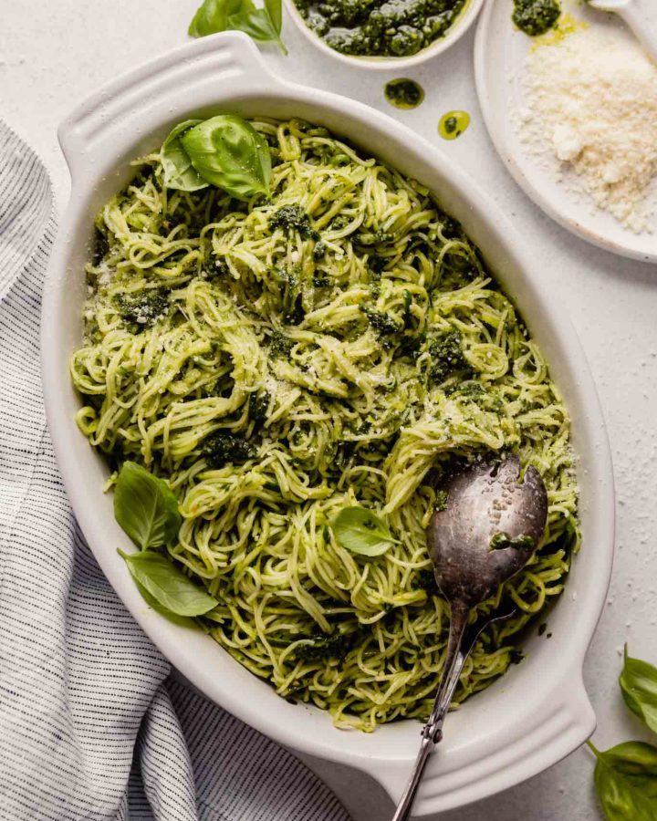 pesto noodles in a white oval dish with cheese and pesto set around