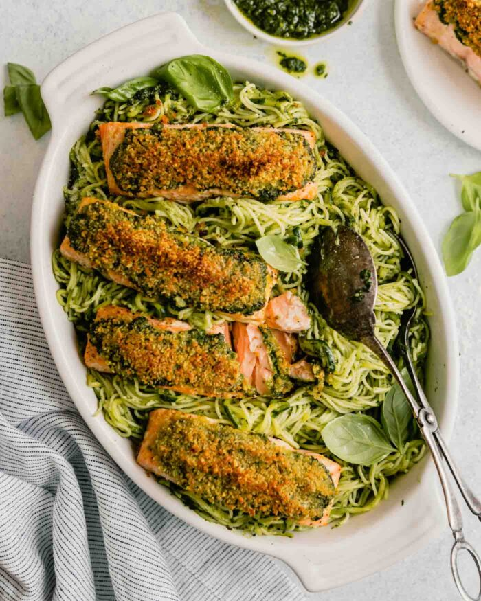 pesto pasta in a white baking dish topped with breaded salmon fillets