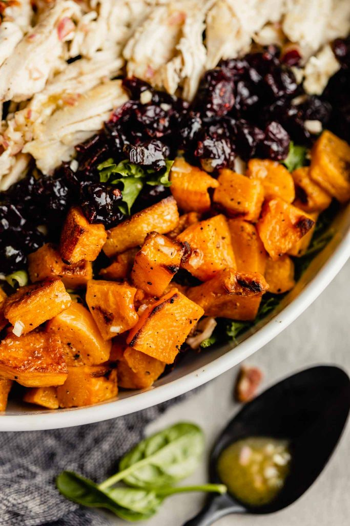 close up of roasted butternut squash in a white bowl filled with lettuce, chicken and cranberries