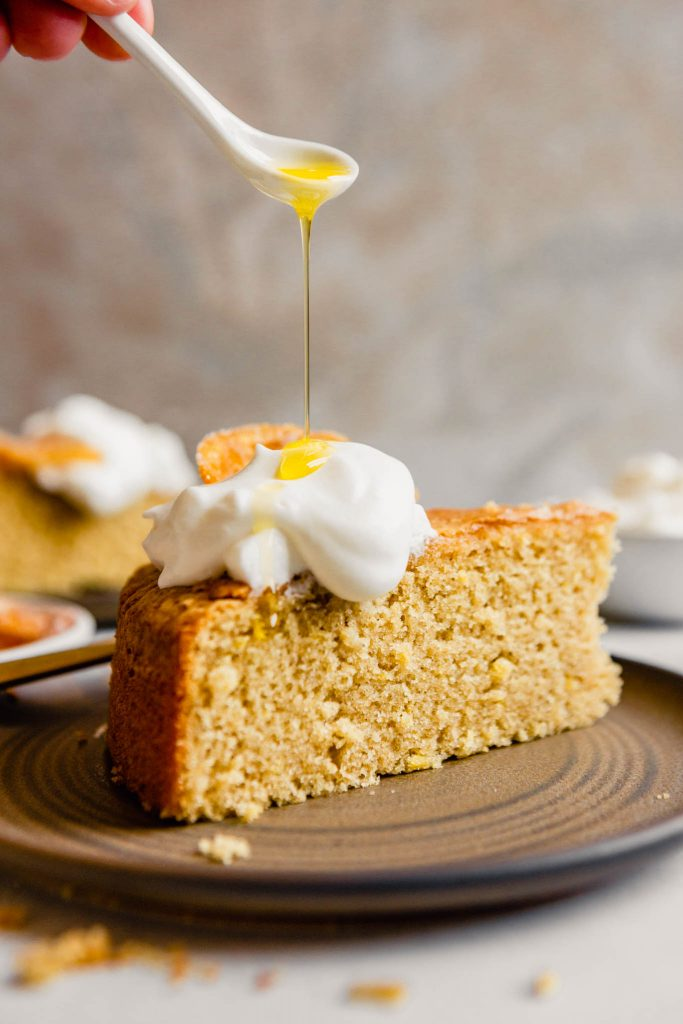 Olive oil being drizzled over a dollop of whipped cream on top of a slice of cake
