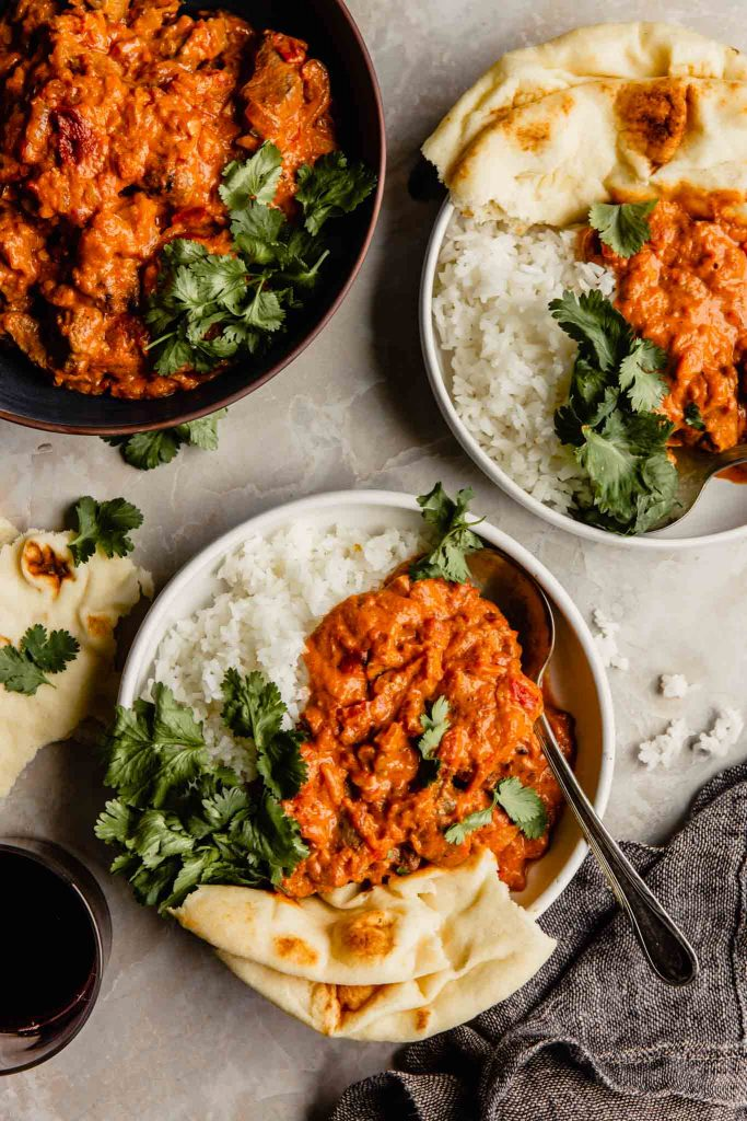 Creamy red sauce over white rice in a bowl with naan bread and cilantro