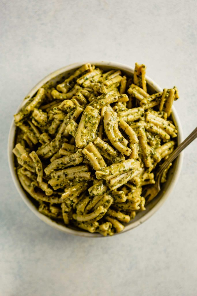 a white bowl filled with pesto-coated pasta.