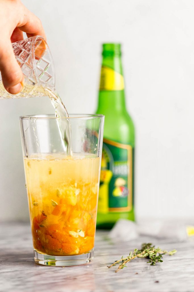 ginger beer being poured into a glass filled with muddled kumquat