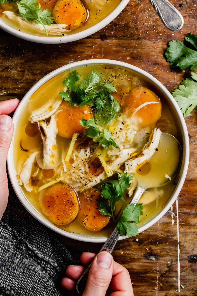 brothy chicken and rice soup with sweet potatoes in a white bowl set on a wood table