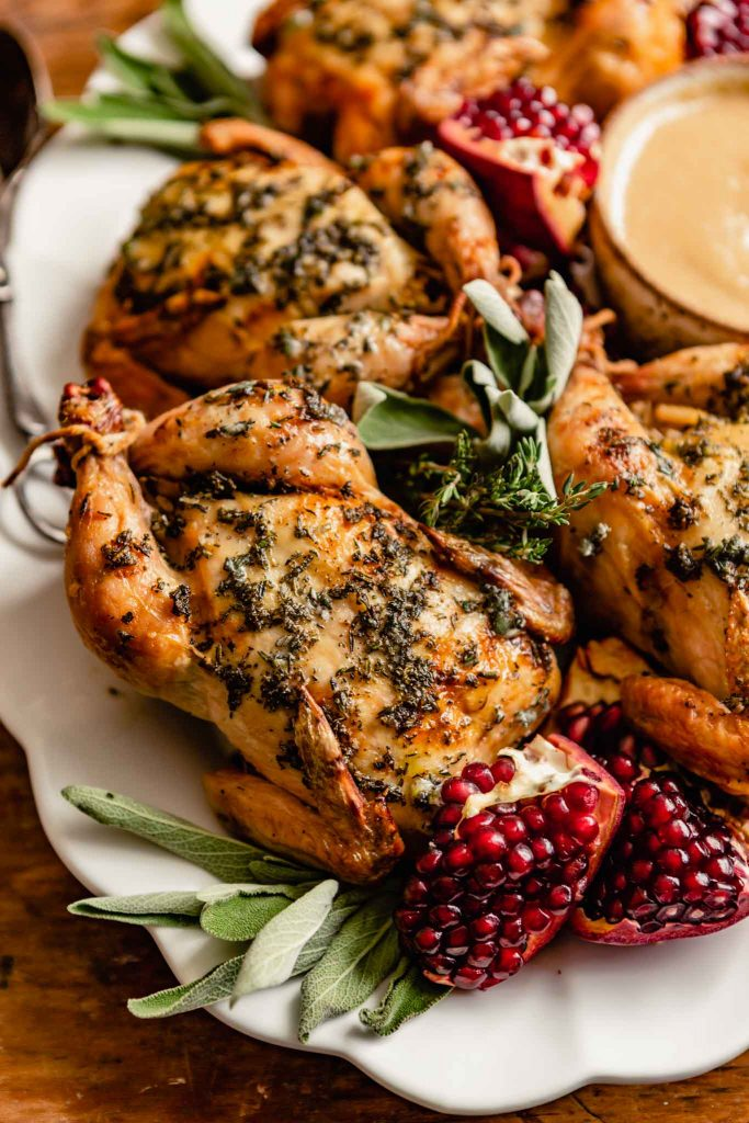 roasted cornish hens on a large white platter garnished with pomegranates, sage, and fresh thyme