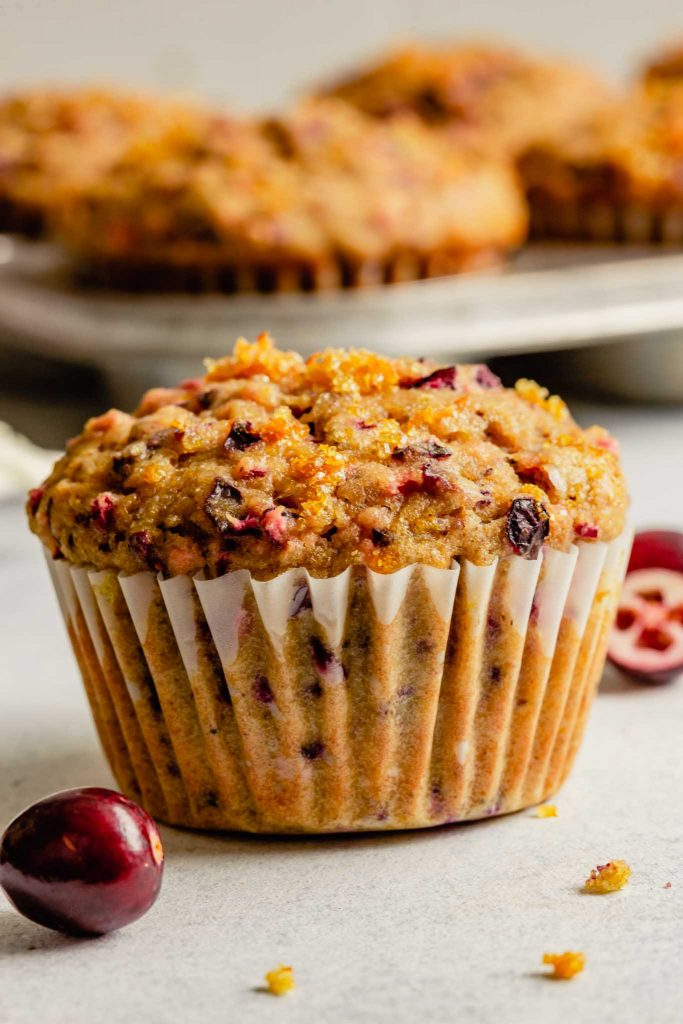 cranberry orange muffin set on a table with more muffins in the background in a muffin tin