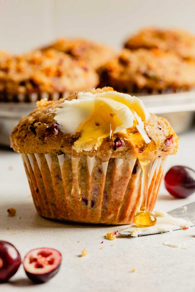 cranberry muffin topped with butter and drizzled with honey