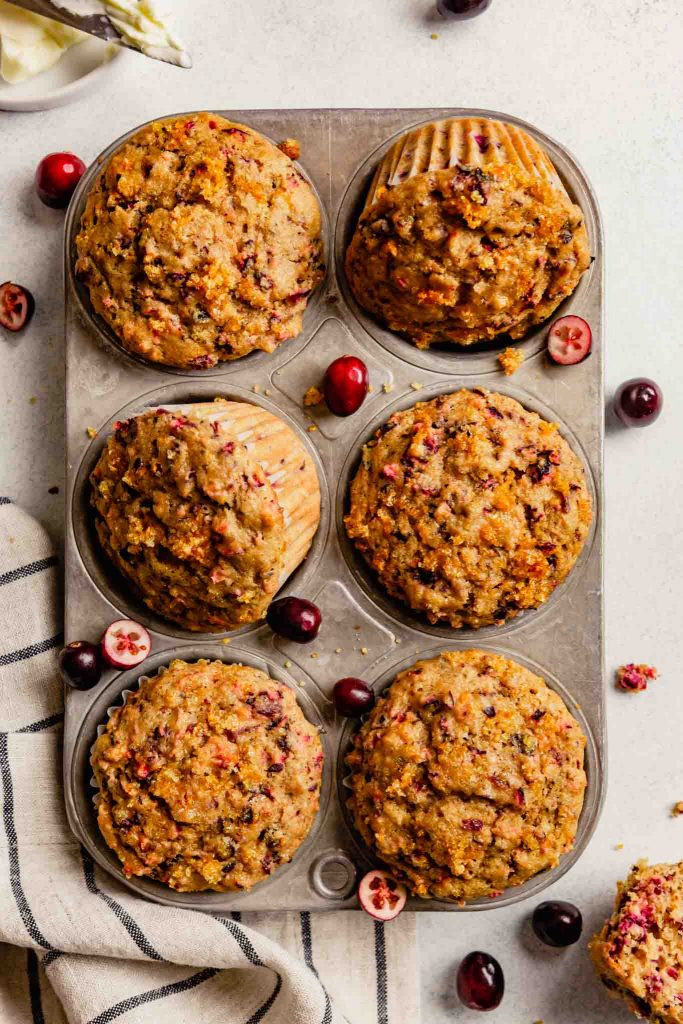 cranberry orange muffins in a muffin tin with cranberries scattered around
