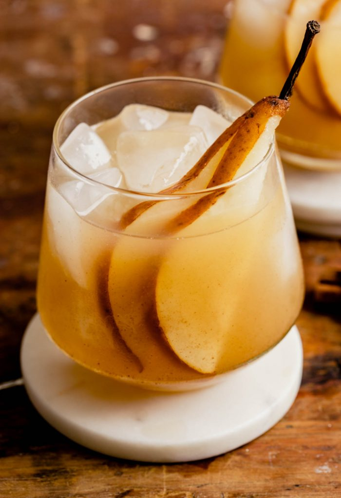 rocks glass set on a white coaster on a wood table filled with a yellow drink and garnished with a pear