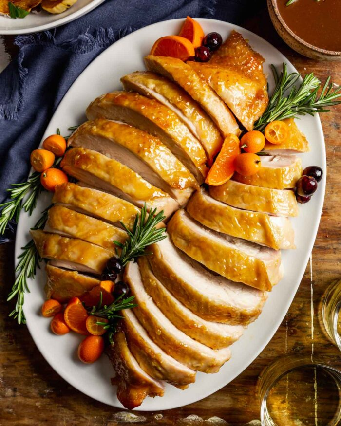 sliced turkey breast on a large white oval set on a wooden table