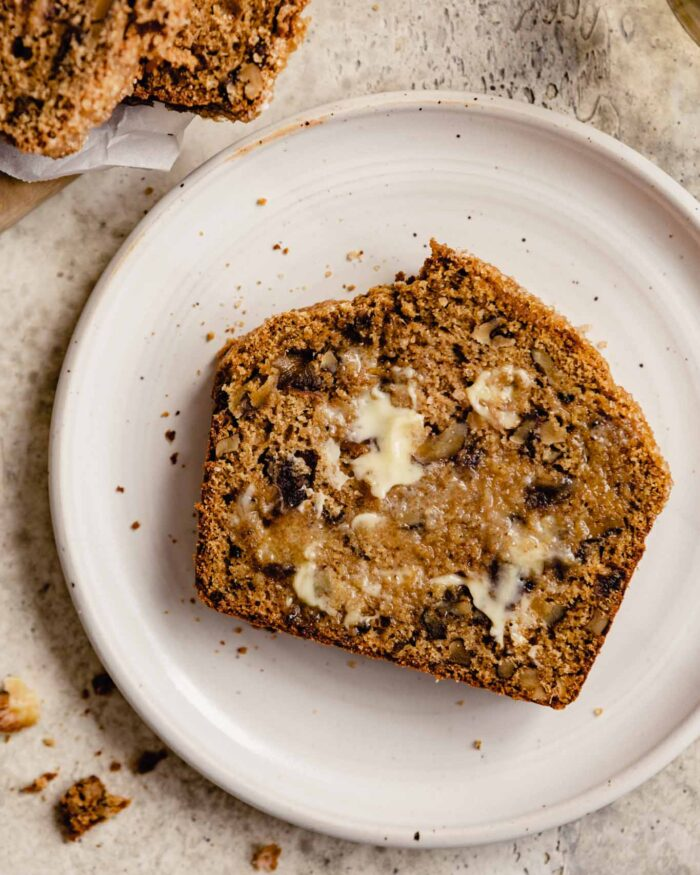 a slice of date nut bread topped with butter on a white plate