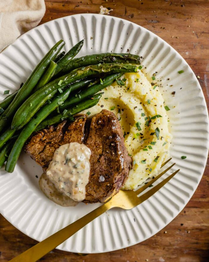 white plates set on a wood table topped with mashed potatoes, pan seared filet mignon, and green beans