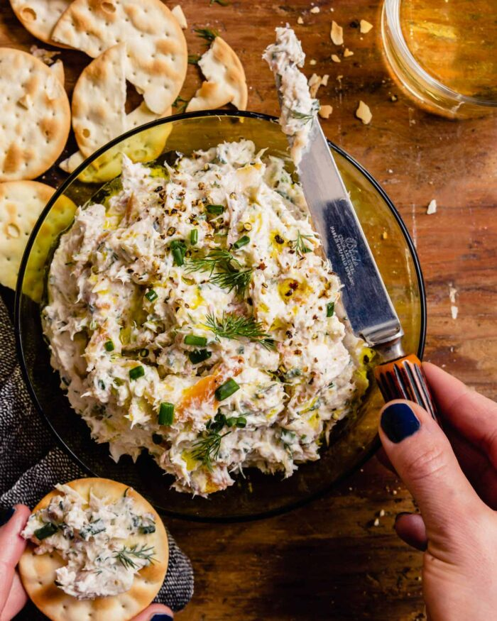 creamy white dip in a green glass bowl with a pair of hands spreading some dip on a cracker