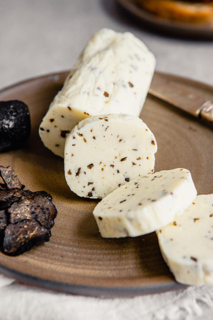 a log of truffle butter set on a brown plate with a few slices cut out of it and laying in a fan
