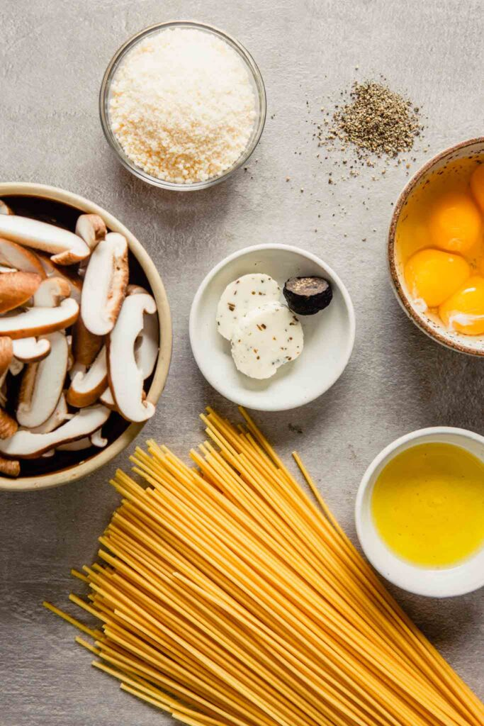overhead of ingredients arranged on a gray background including truffle butter, pasta, eggs, mushrooms, parmesan