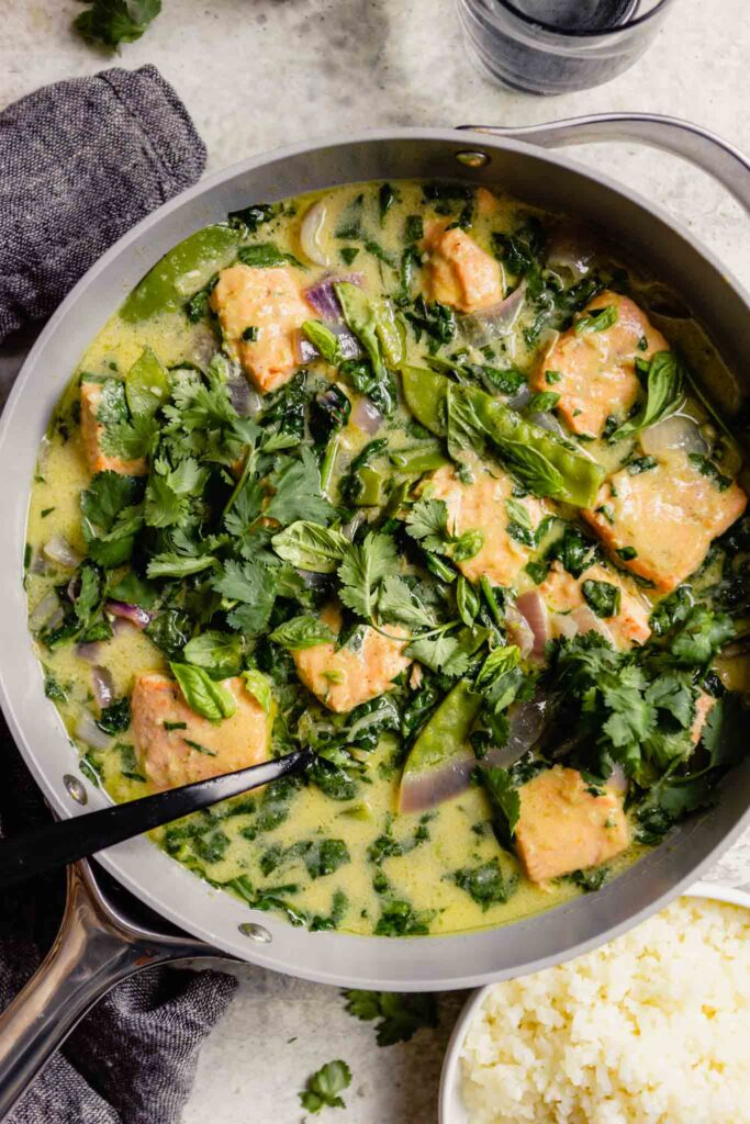 large gray saute pan filled with green coconut curry sauce, green vegetables and large chunks of salmon